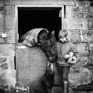 Boy with horse and dog in stables in Duns Scottish Borders family photography session
