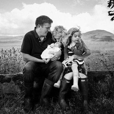 Family with newborn and toddler in their garden with scenic views in Jedburgh Scottish Borders family photography session