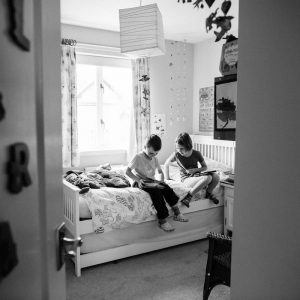 Brother and sister playing ipads in bedroom in Kelso Scottish Borders family photography session